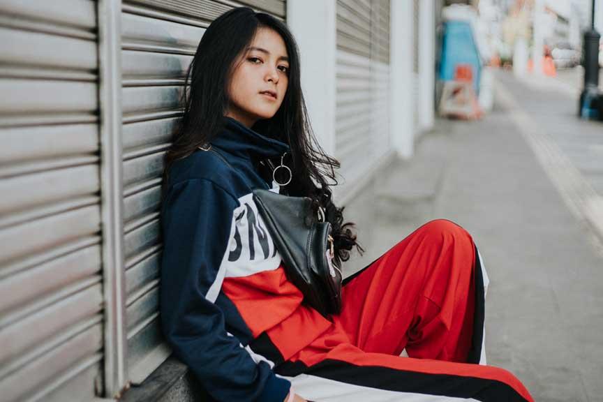 A teenage girl sitting on a street path