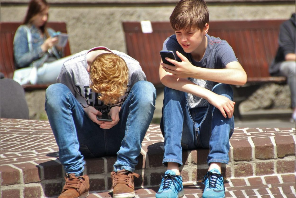 2-boy-sitting-on-brown-floor-while-using-their-smartphone-159395